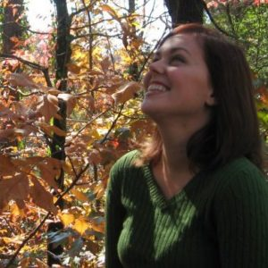 Person in a green sweater stands among autumn trees, looking up and smiling.