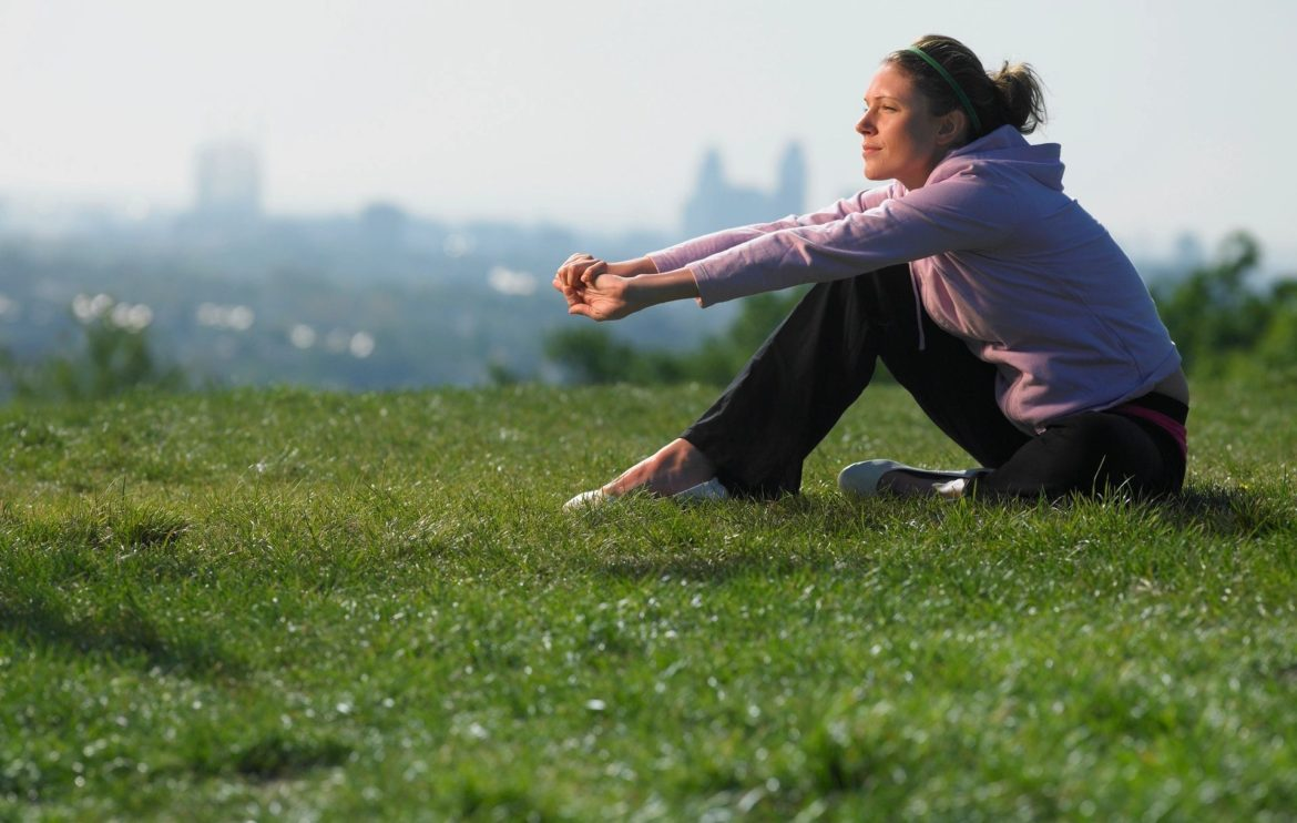 Woman sits in the grass, arms stretched out with her elbows on her knees.